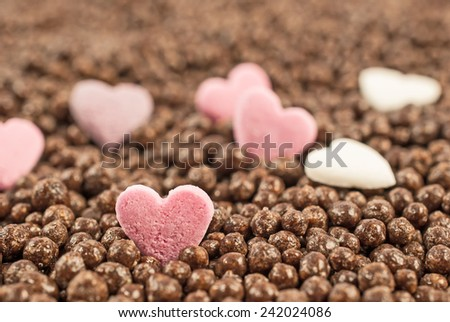 Pink heart on chocolate balls background, shallow depth of field. Valentines day background idea - stock photo