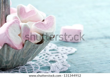 Pink heart shaped marshmallows in a metal cupcake on light blue wooden background, with copy space - stock photo