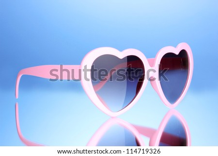 Pink heart-shaped sunglasses on blue background - stock photo