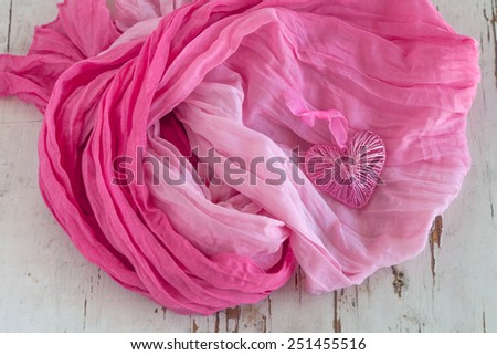 Pink heart with scarf on rustic background - stock photo