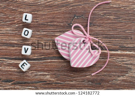 pink hearts on wooden board with letters love - stock photo