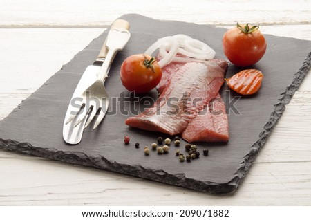 pink herring with tomato, carrot, onion and pepper on slate plate - stock photo