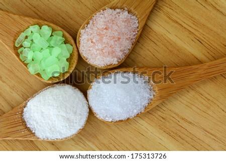 Pink Himalayan Salt, Sea Salt, Mountain Salt and Epsom Salt in a wooden spoon - stock photo