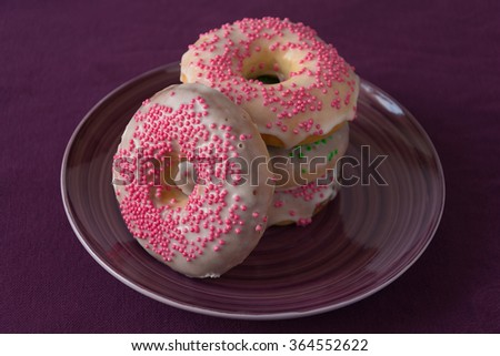 Pink homemade donuts on purple background - stock photo