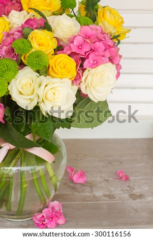 pink hortensia flowers with white and yellow roses in vase  close up - stock photo
