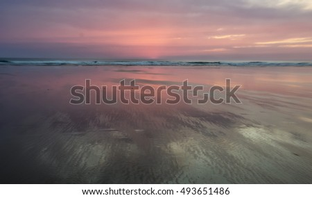 Pink hues of sunset reflected in the wet sand