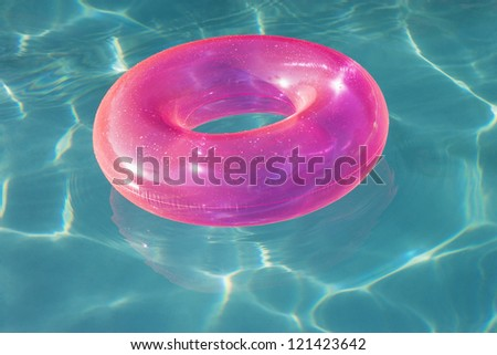 Pink inflatable tube floating on water in swimming pool - stock photo