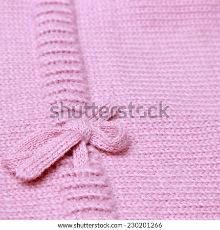 Pink knitting background of handmade woolen pattern with lovely bow - stock photo