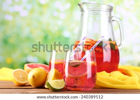 Pink lemonade in glasses and pitcher on table on natural background - stock photo