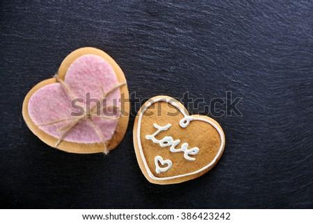 Pink love cookies on dark background, closeup - stock photo