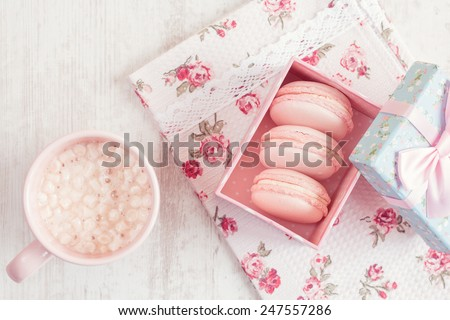 Pink macaroons in gift box with cup of coffee. Pastel colored. Top view - stock photo