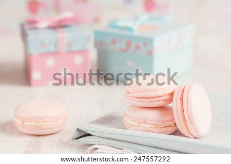 Pink macaroons with gift boxes on background. Pastel colored - stock photo