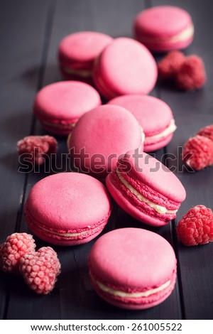 Pink macaroons with raspberries on black wooden background - stock photo