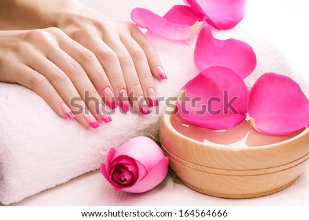 pink manicure with fragrant rose petals and towel - stock photo