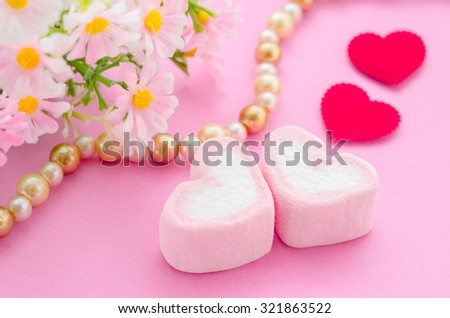 Pink marshmallow herat shape with red paper heart and flower on pink background. Love concept.