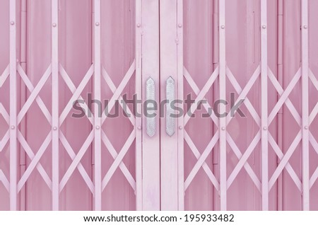 Pink metal grille sliding door with aluminum handle - stock photo