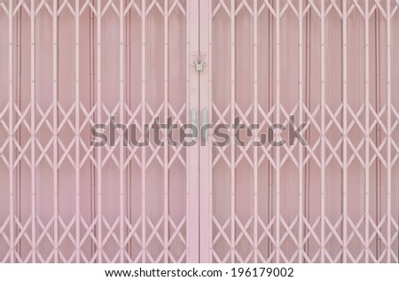 Pink metal grille sliding door with pad lock and aluminium handle - stock photo