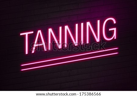 Pink neon sign with tanning text on wall - stock photo