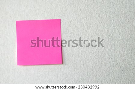 Pink note pad on white wall, template - stock photo
