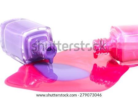 Pink, orange and purple nail polish bottles with nail polish pouring from them on the white background - stock photo