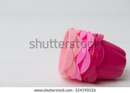 Pink, orange and red silicone baking cups for muffins or cupcakes on white - stock photo