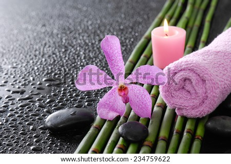 pink orchid and bamboo grove, candle ,towel on wet black background  - stock photo