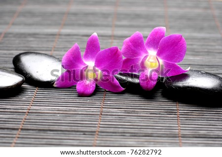 Pink orchid and zen Stones on bamboo mat - stock photo