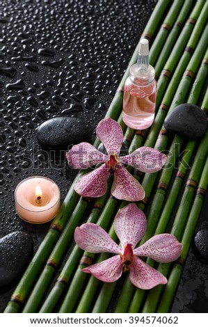 Pink orchid ,stones,oil,bamboo grove ,candle, oil on wet black background   - stock photo