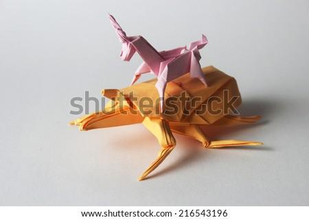 Pink origami unicorn riding orange origami bug - stock photo