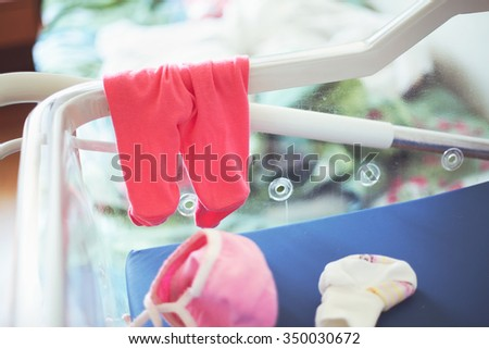 Pink panties and little baby cap in hospital cradle for newborns - stock photo