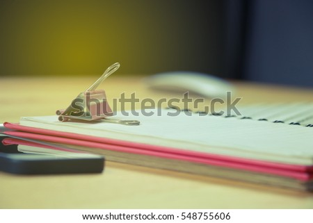 Pink paper clip placed on a notebook. Placed on the desk