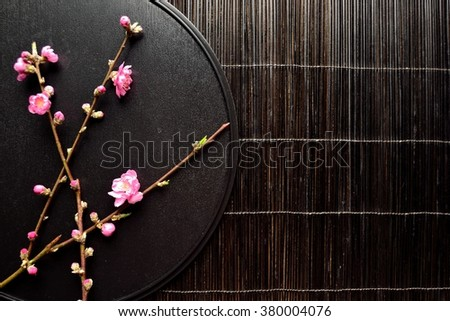 Pink peach blossoms on the black tray.Image of Japanese style flower arrangement on spring season - stock photo