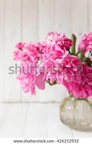 Pink peonies bouquet in vase on wooden background