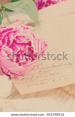 Pink peony with vintage letter on white lace background, retro toned - stock photo