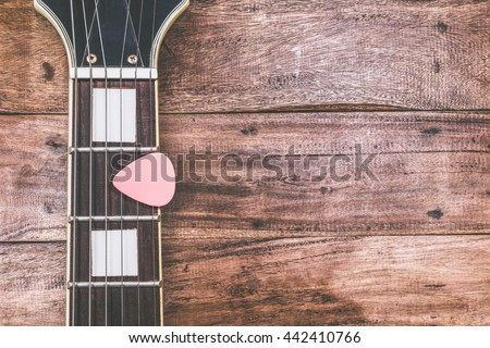 pink pick & electric guitar fretboard, on old wood + vintage filter for music background - stock photo