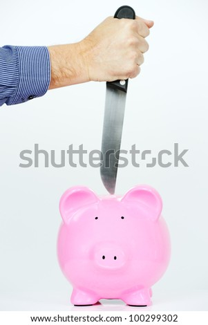 pink piggy bank and arm with knife