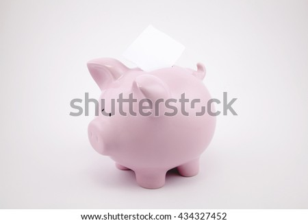 Pink piggy bank and blank sheet of paper with copy space for text message  - stock photo