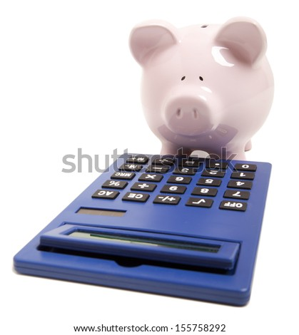 Pink piggy bank and calculator isolated on white background