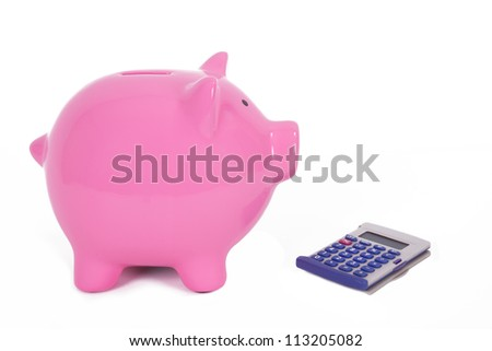 Pink piggy bank near calculator, isolated on white background. - stock photo