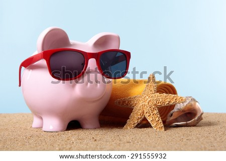 Pink piggy bank on a beach with sunglasses, retirement or vacation savings planning.