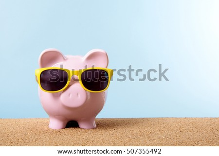 Pink piggy bank on a beach with yellow sunglasses.  Space for copy. Travel money concept.
