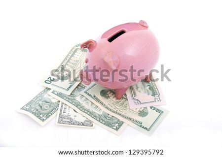 Pink piggy bank on dollars - stock photo