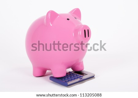 Pink piggy bank on the calculator, isolated on white background.