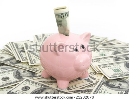 pink piggy bank sitting on top of hundred dollar bills - stock photo