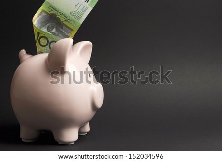 Pink Piggy Bank with Australian 100 hundred dollar note against a black background, for savings concept, with copy space. - stock photo