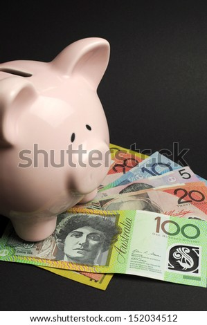 Pink Piggy Bank with Australian money against a black background, for savings concept. Vertical. - stock photo