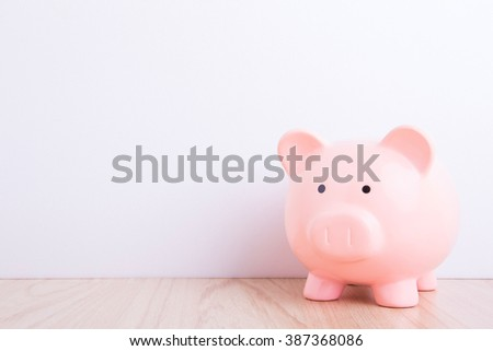 pink piggy bank with white wall background, great for your design - stock photo
