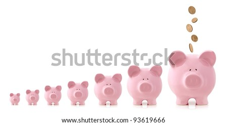 Pink piggy banks increasing in size, with coins falling into largest one.  Growing investment concept. - stock photo