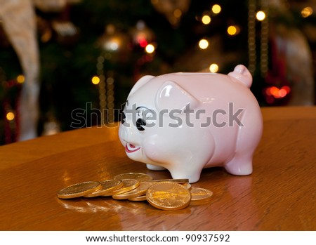 Pink piggybank on a wooden table in front of a christmas tree with gold coins - stock photo