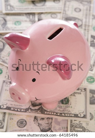 pink piggybank with american dollars - stock photo